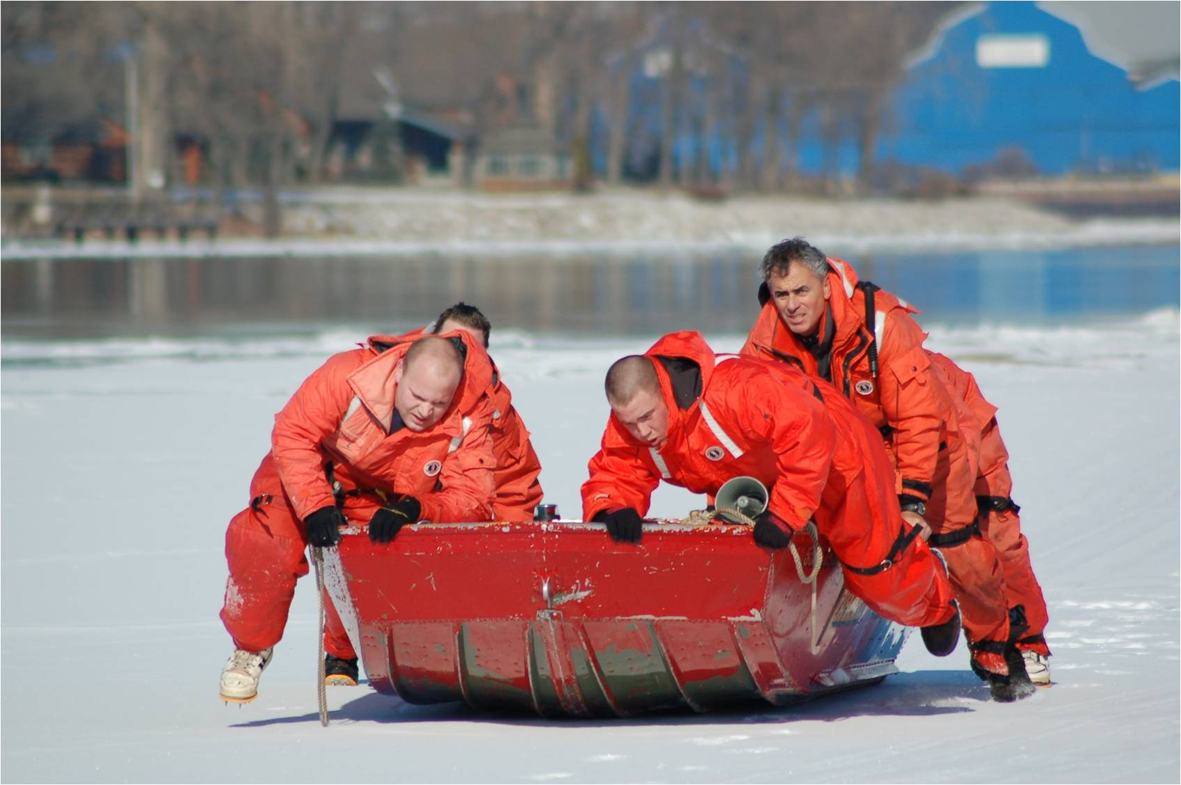 four firefighters practicing ice water rescue