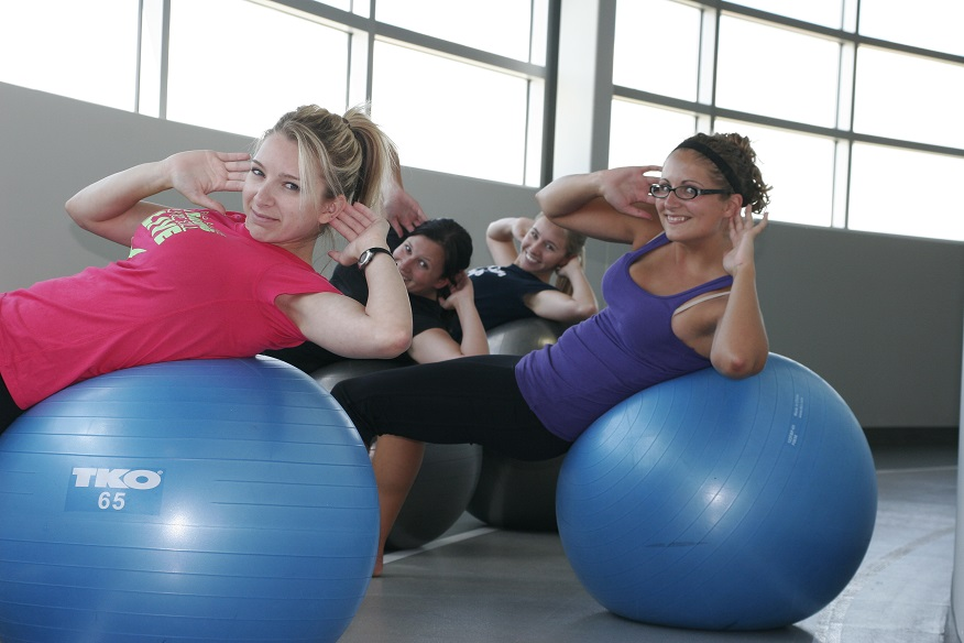 four fitness staff exercising on large exercise balls
