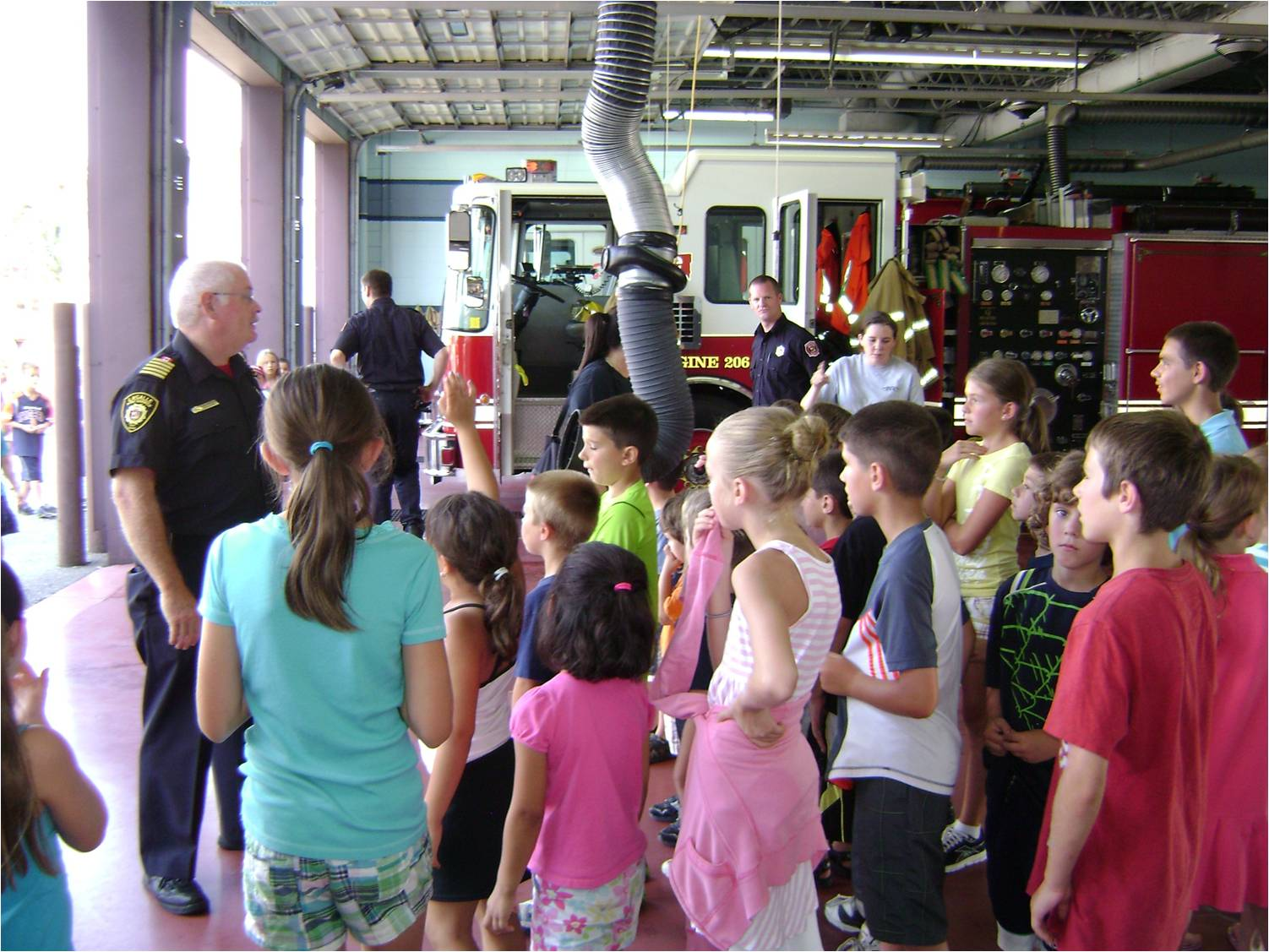 Chief Sutton giving a Fire Hall tour to school-aged children