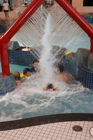 Swimmers getting wet from an overhead water feature