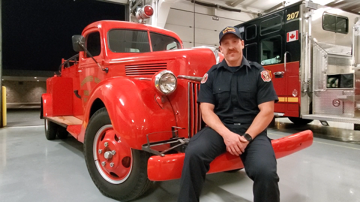 Firefighter sitting on antique truck